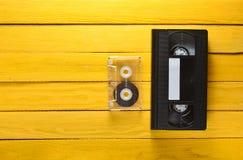 VHS-Videokassette und Audiokassette auf einem gelben hölzernen Hintergrund Retro- Medientechnik von den achtziger Jahren Beschnei Stockbild