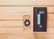 Vhs wideo kaseta i audio kaseta na żółtym drewnianym backgro fotografia stock
