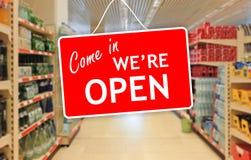 Vi är den öppna etiketten på en abstrakt supermarketbakgrund Royaltyfria Bilder
