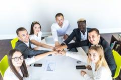 Vi är det stora laget Grupp av lyckligt affärsfolk som tillsammans rymmer händer, medan sitta runt om skrivbordet royaltyfri foto