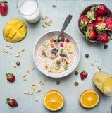 维生素丰富的早餐、燕麦粥与坚果和干果子,草莓和芒果,新鲜的汁液在木土气背景上面vi 免版税图库摄影