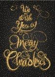 Vi auguriamo una cartolina d'auguri brillante dell'oro di Buon Natale, frase di calligrafia Progettazione di iscrizione Vettore d Immagine Stock