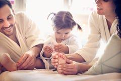 Vi behöver massera fot till vår liten flicka unga lyckliga föräldrar Arkivbilder