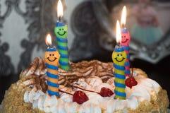 Vi firar födelsedagen, kaka med brinnande stearinljus arkivfoto