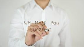 Vi hjälper dig att lyckas, skriftligt på exponeringsglas Royaltyfri Fotografi