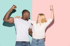 Vi segrade Man och kvinna för vinnande framgång som lycklig afro firar vara en vinnare Dynamisk bild av den caucasian kvinnlign o royaltyfria foton