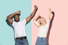 Vi segrade Man och kvinna för vinnande framgång som lycklig afro firar vara en vinnare Dynamisk bild av den caucasian kvinnlign o royaltyfri foto
