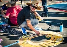 Via Arte- Artists creating chalk art on streets 20 year anniversary. Close up of an artist at Via Arte event creating an chalk drawing in the street. 20 year royalty free stock photos