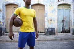 Via brasiliana del villaggio della palla della tenuta di calcio del giocatore di football americano fotografia stock libera da diritti