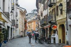 Via commerciale durante il giorno piovoso nella città alpina italiana di Aosta in Italia nordoccidentale Immagine Stock Libera da Diritti
