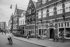 Via con i ristoranti, i negozi, il ciclista e la gente passeggianti nello s-Hertogenbosch in città fotografia stock