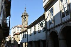 Via con la torre di chiesa, le pareti bianche, le finestre verdi e le iluminazioni pubbliche Santiago de Compostela spain immagine stock