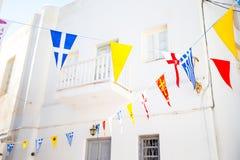 Via con le bandiere variopinte in Mykonos, Grecia Immagini Stock