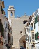 Via con una grande chiesa in Mahon, Menorca Fotografia Stock