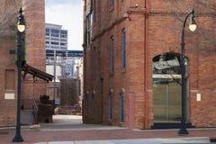 Via del centro con le costruzioni di mattone e la posta della lampada Immagini Stock Libere da Diritti