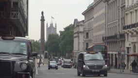 Via del centro di Londra con il doppio Decker Red Bus di traffico di automobile ed i taxi della carrozza stock footage