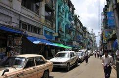 Via del centro di Yangon con le vecchie case ed automobili Immagine Stock Libera da Diritti