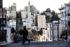 Via dell'incrocio della persona sulla collina ripida a San Francisco con le costruzioni impilate sopra a vicenda nel fondo Fotografie Stock