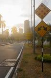 Via della città al crepuscolo con le tracce della luce e il signm di traffico Fotografie Stock Libere da Diritti