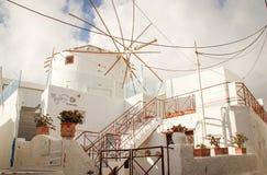 Via della città di Fira con le case bianche e gli otturatori blu Costruzione accogliente dell'hotel con un mulino a vento bianco fotografia stock