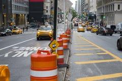 Via della città di Manhattan con i barilotti della costruzione e del traffico cittadino immagini stock