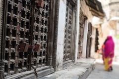 Via della città di Zanzibar con allontanarsi delle porte e di wooman del ferro Fotografia Stock