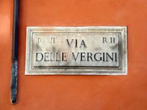 Via Della Vergini, Marble Street Sign, Rome, Italy. An aged marble street sign, or plaque, Via Della Vergini, attached to a brown stucco wall, Old Rome, Italy stock photography