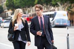 Via di And Businesswoman In dell'uomo d'affari con caffè asportabile Immagine Stock