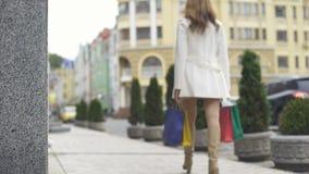 Via di camminata femminile alla moda della città che tiene i sacchetti della spesa, vendita urbana di consumismo archivi video