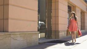 Via di camminata shopaholic femminile con le borse, consumismo, acquisto dei regali, vendita video d archivio