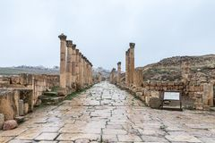 Via di Cardo Maximus che conduce dalla plaza ovale nella grande città romana di Jerash - Gerasa, distrutta da un terremoto in ANN fotografia stock libera da diritti