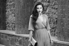 Via di seta del partito del vestito dalla bella passeggiata castana sexy della donna Fotografia Stock