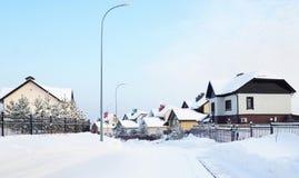 Via di Snowy con i cottage nel villaggio di inverno Immagini Stock Libere da Diritti