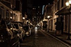 Via di vecchia città di notte con la pietra per lastricati, accesa dalle lampade di via con le automobili parcheggiate Fotografia Stock