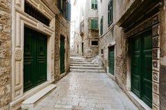 Via europea stretta con le porte verdi nel centro storico di Sibenik, Croazia Immagini Stock Libere da Diritti
