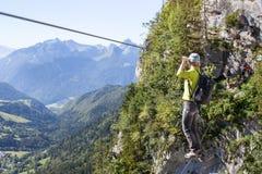 Via il ferrata che scala, donna in ponte di corda dell'incrocio del cablaggio nelle montagne Fotografia Stock
