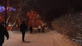 Via innevata della città di inverno con il passaggio sulla sua gente nella notte polare stock footage