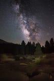 Via Látea do verão e centro galáctico com o rio de fluxo de A no primeiro plano em prados de Tuolumne, parque nacional de Yosemit