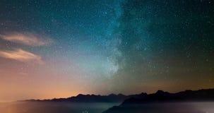 Via Látea e estrelas do lapso de tempo de Astro que giram sobre os cumes com névoa e nuvens vídeos de arquivo