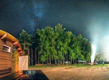Via Lattea sopra il fuoco della casa e del campo della montagna Fotografie Stock Libere da Diritti