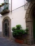 Via medievale con sollievo ceramico, il vaso del pavimento, i balconi con i fiori e lo stucco Immagini Stock Libere da Diritti