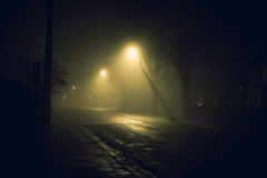 Via nebbiosa alla notte immagine stock