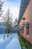 Via nevicata lungo il muro di mattoni dell'edificio per uffici Fotografia Stock Libera da Diritti