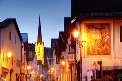 Via principale stretta nell'ora blu con le case dipinte in Baviera immagini stock