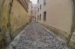 Via stretta con un percorso delle pietre per lastricati Attraversi fra i vecchi grattacieli storici a Leopoli, Ucraina immagine stock