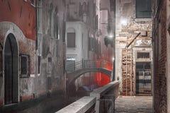 Via stretta di notte con un canale idrico a Venezia fotografia stock