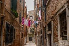 Via stretta a Venezia Sopra la via sulla corda da bucato appesa ha appeso i vestiti lavati Fotografia Stock Libera da Diritti