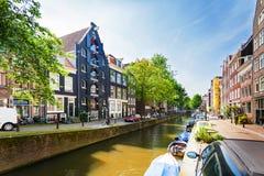 Via tipica a Amsterdam con il canale e le case variopinte netherlands fotografia stock