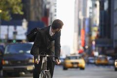 Via urbana di Riding Bicycle On dell'uomo d'affari Fotografia Stock