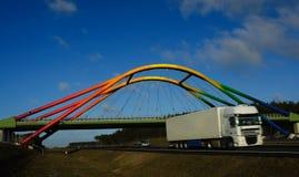 Viaduc d'arc-en-ciel au-dessus d'omnibus avec déménager de camion Image libre de droits